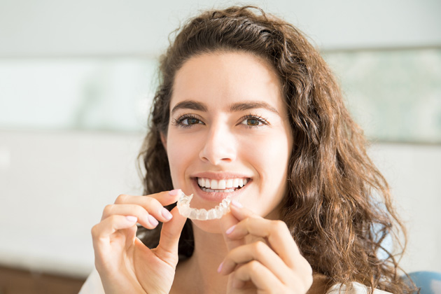 Diese junge Frau freut sich über ihre unsichtbare Zahnschiene